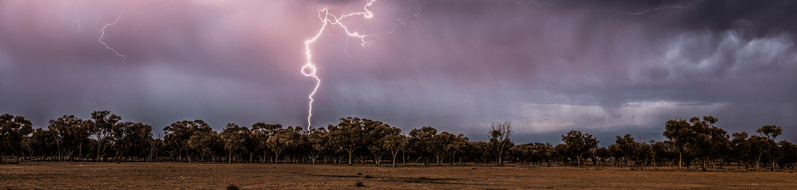 Lightning strikes over an empty field.