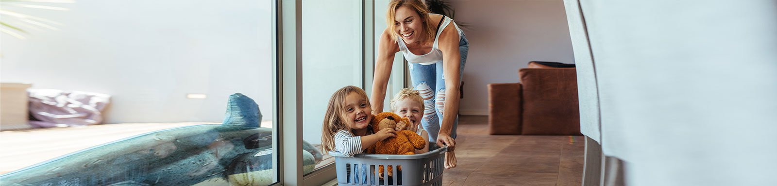 Mother pushing laundry basket with children