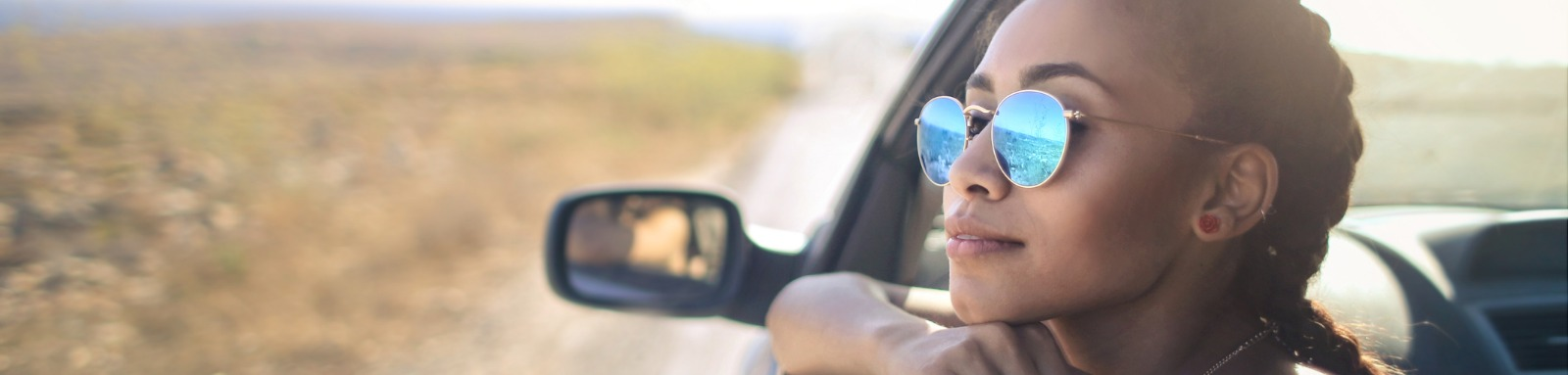 Woman in sunglasses looking at empty landscape from car